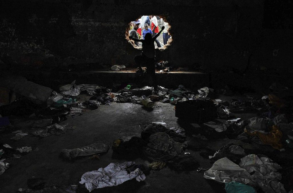 A young boy jumps through a hole as others peer through the wall of a cell at Muzenze Prison in Goma